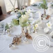 Christrosen in Christbaumkugeln als Tischdeko