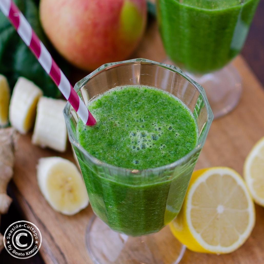 Grüner Smoothie in einem Glas mit rot gestreiftem Strohhalm, von oben gesehen, Bananenstücke, aufgeschnittene Zitrone und Apfel daneben dekoriert
