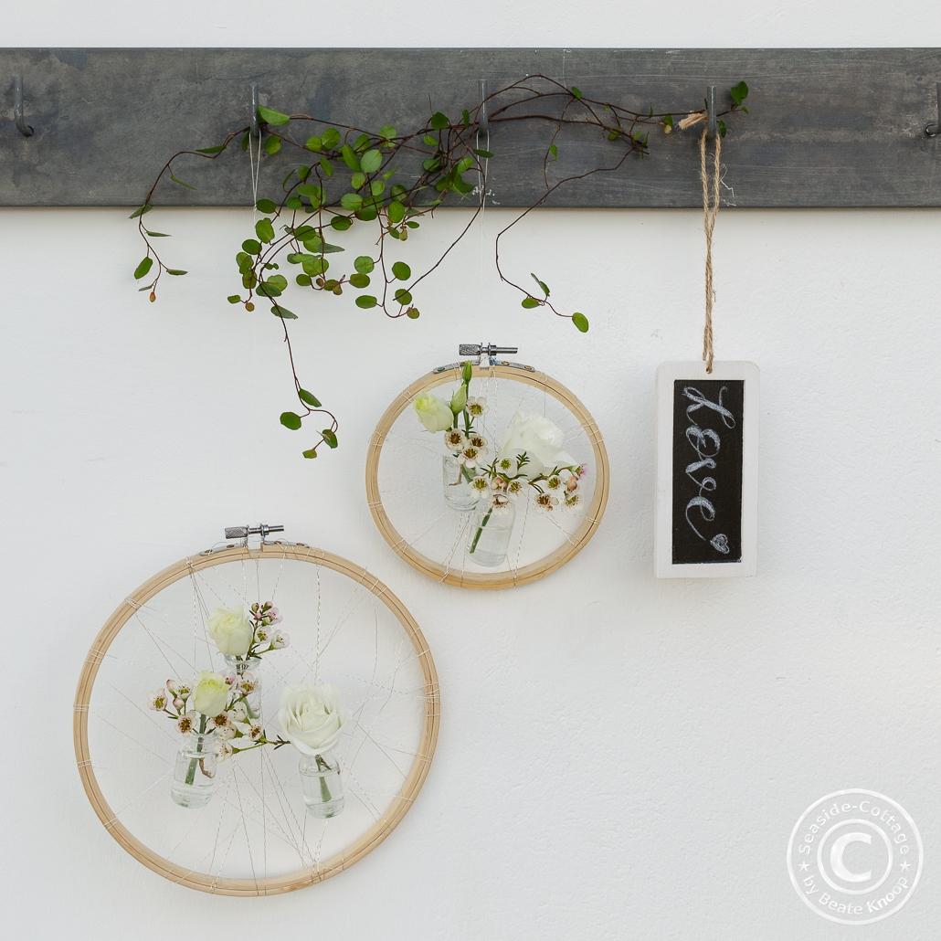 Stickrahmen als Wanddeko mit kleinen Blumenvasen mit Waxflower und Eustoma