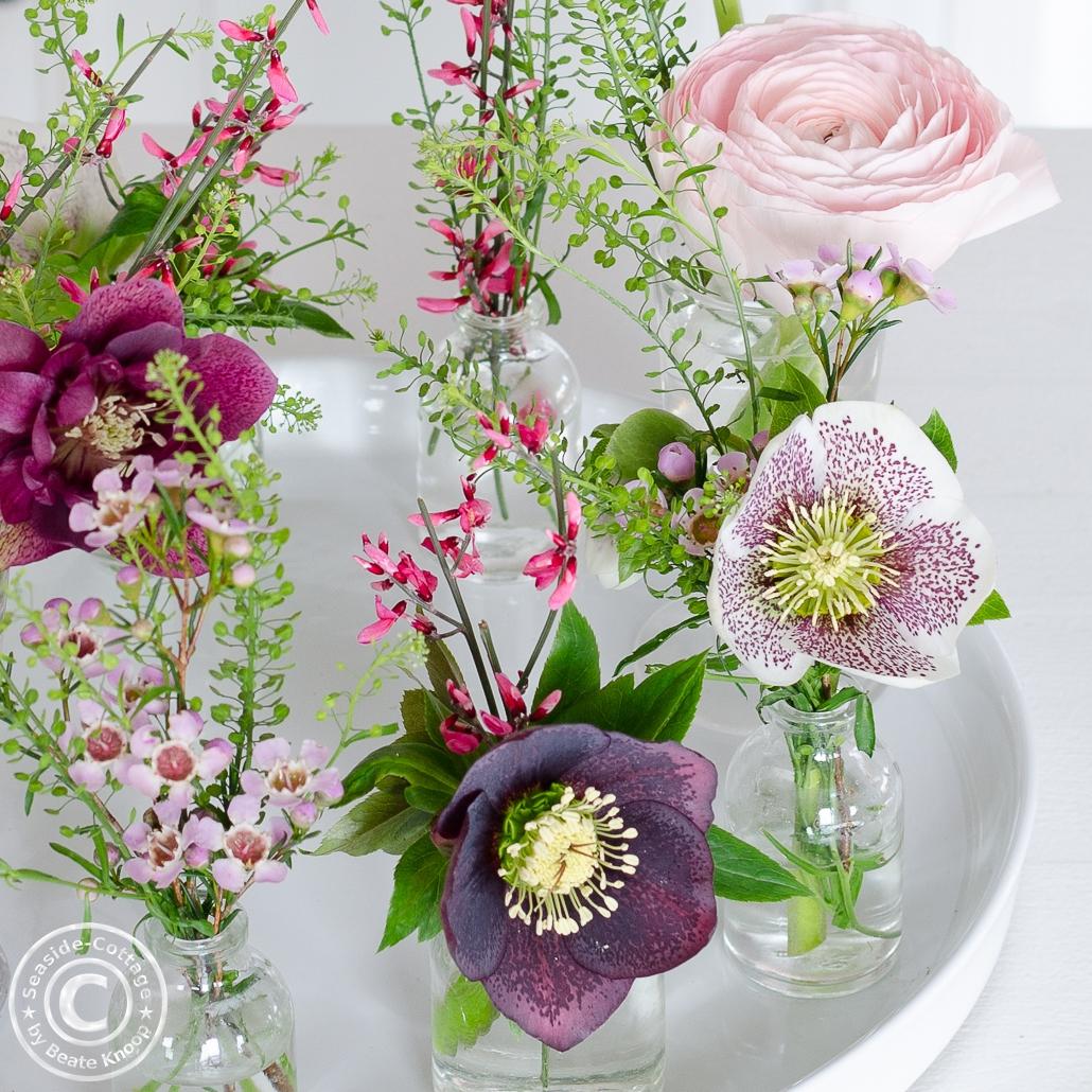 Blumendeko mit Ranunkeln und Lenzrosen in kleinen Vasen