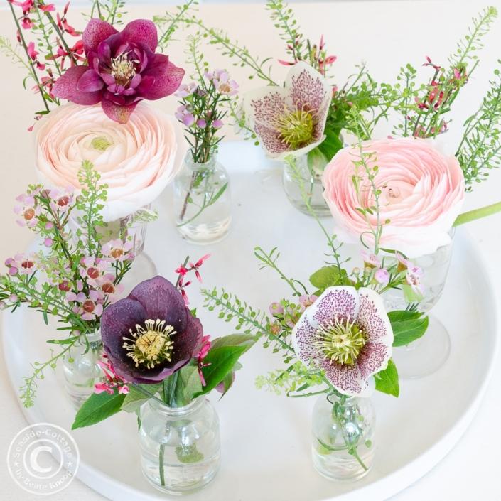 Blumendeko mit Frühlingsblumen in kleinen Vasen