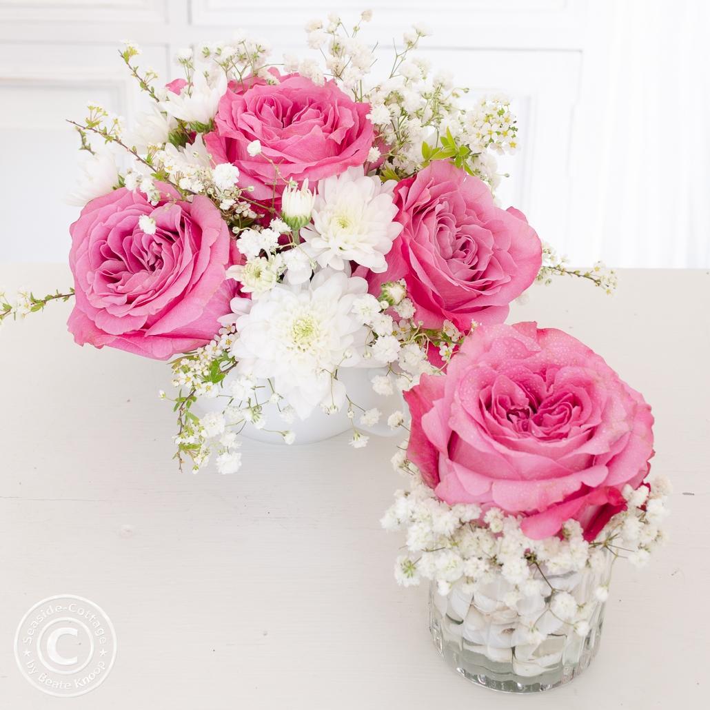 Blumendeko mit Rosen und Schleierkraut in rosa und weiß