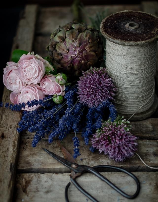dunkles stilleben mit artischocke, rosa Rosen und Lavendel