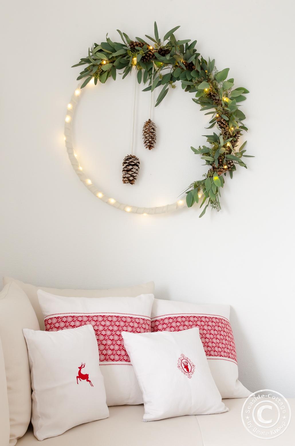 Weihnachtliche Deko mit Kissen und Wandkranz aus Eukalyptus, weißem Filz und mit Lichterkette