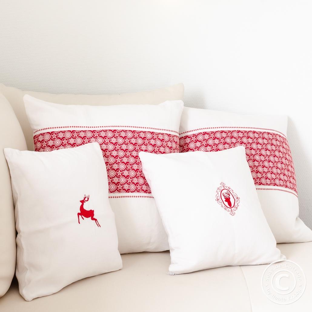Weihnachtliche Kissen aus altem weißen Leinen bestickt mit roten Hirschen