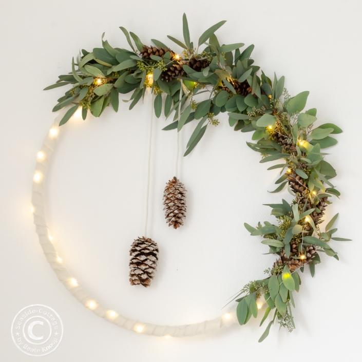 weihnachtliche Wanddeko mit Hulahoop bewickelt mit Eukalyptus, weißem Filz und Lichterkette