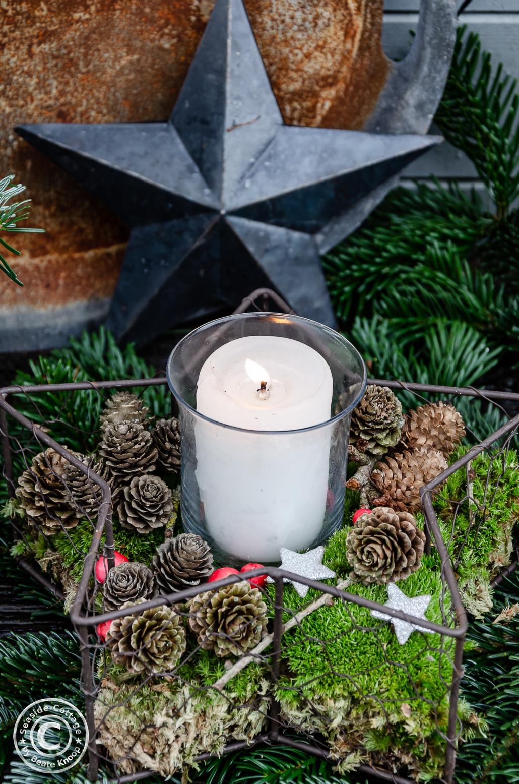 Weihnachtsdeko mit Kerze, Moos, Zapfen im Garten