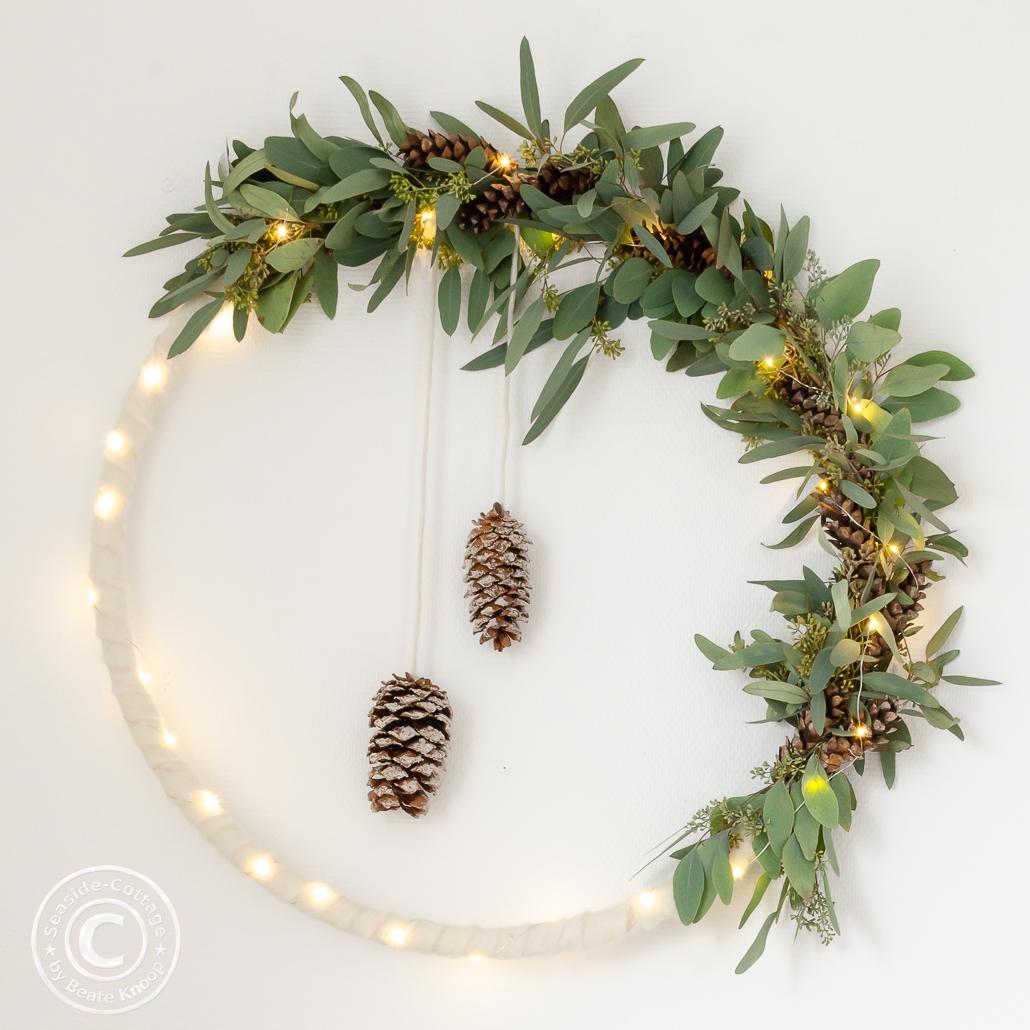 Winterlicher beleuchteter Hulahoop Kranz mit weißem Filz, Eukalyptus und Zapfen