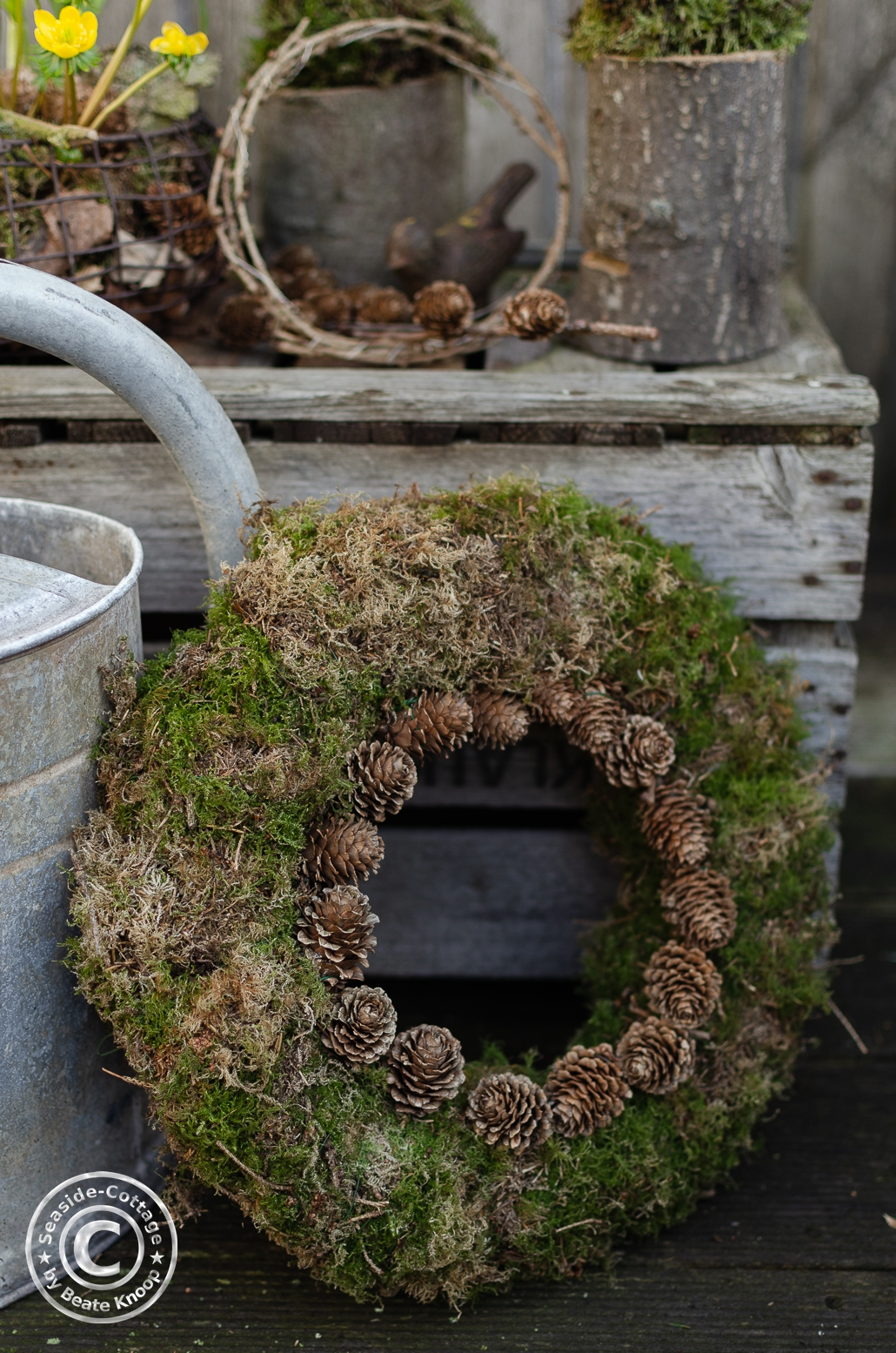 Naturnahe Gartendeko mit Mooskranz, verziert mit Lärchenzapfen, angelehnt an eine Zinkgießkanne und einer alten Holzstiege