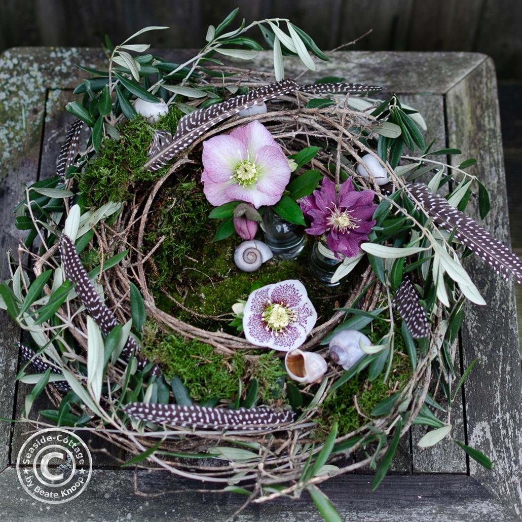 Nest aus Rebe mit Olivenzweigen, Moos und Lenzrosen dekoriert