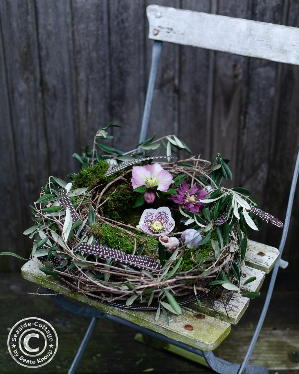 Weißer Gartenstuhl mit einem Nest aus Rebe, dekoriert mit Olivenzweigen, Moos und Lenzrosen