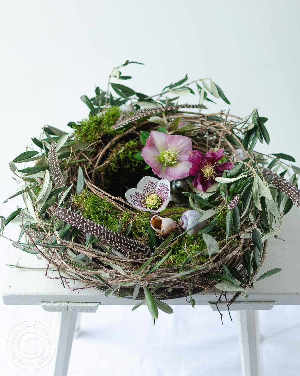 weißer Holzhocker mit einem Nest aus Rebe, dekoriert mit Olivenzweigen, Moos und Lenzrosen