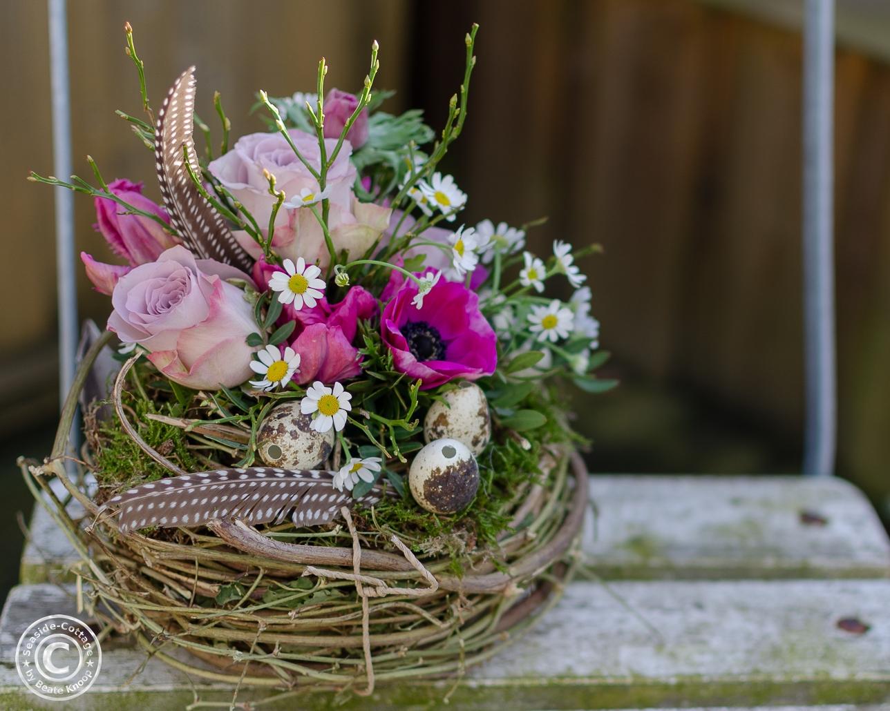 Nest mit frischen Frühlingsblumen in pink-rosa Tönen: Anemonen, Tulpen, Rosen, Edelkamille, Heidelbeergrün Wachteleier und Federn