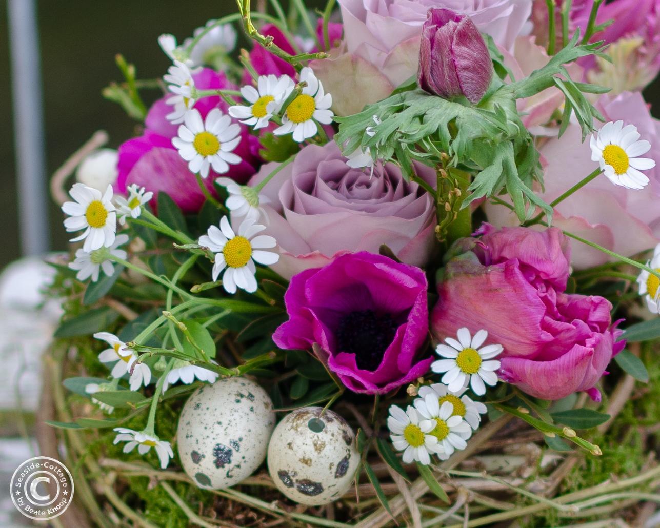 Nahaufname Frühlingsblumen in pink-rosda Tönen: Anemonen, Tulpen, Rosen, Edelkamille, Wachteleier
