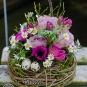 Nest aus Hopfenrebe geüllt mit pinkfarbenen Anemonen und Tulpen, fliederfrabenen Rosen, Edelkamille, Heildebeergrün und Wachteleiern