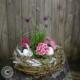 Frühlingsblumen in Rosa Farben in einen Rebenkranz gepflanzt