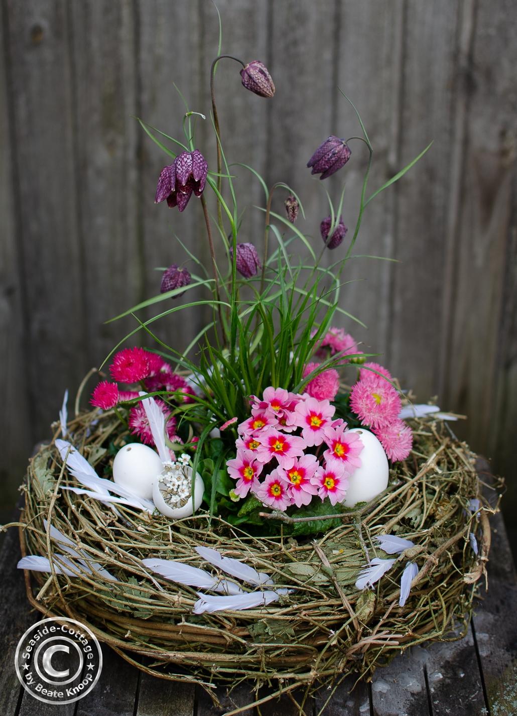 Osternest mit rosa Frühlingsblumen