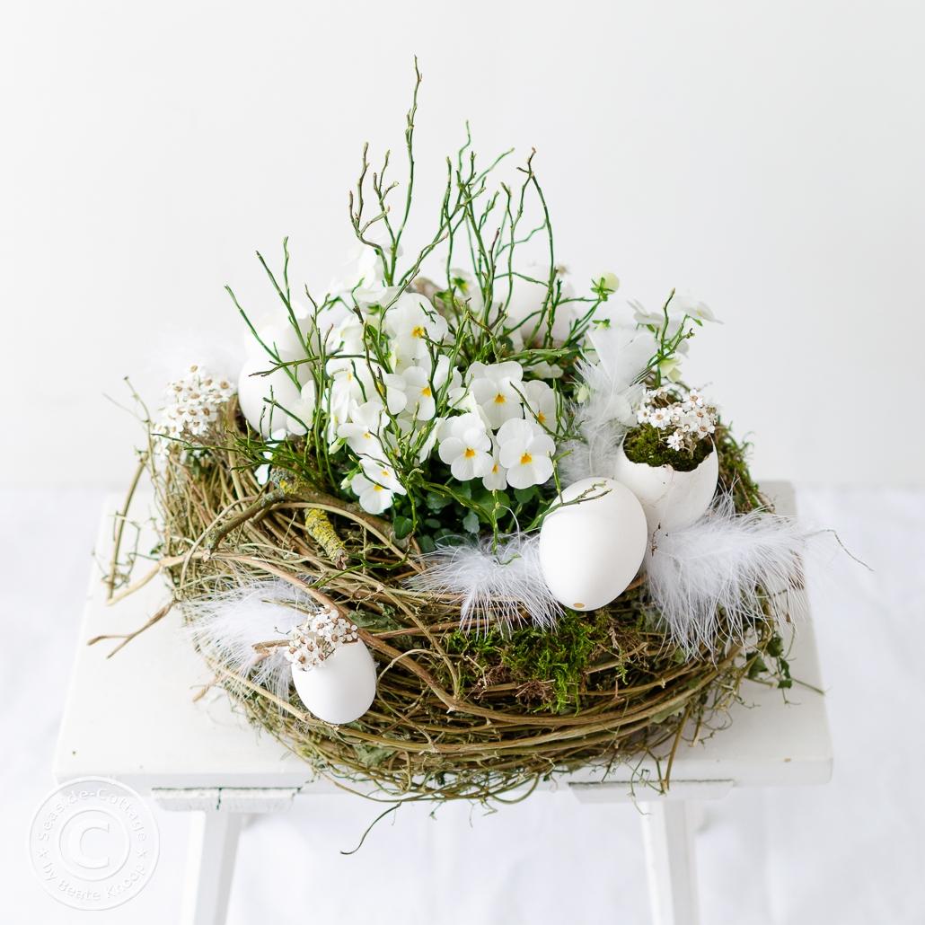 Osternest in Weiß mit Hornveilchen bepflnazt und mit Gänseeiern und Federn dekoriert auf einem alten weißen Holzhocker