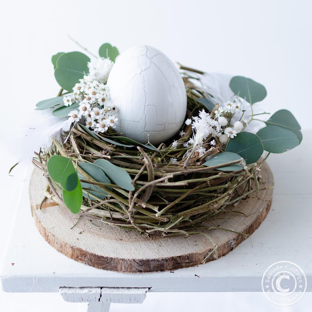 Kleines Nest mit Trockenblumen auf einer Baumscheibe, dekoriewrt mit Eukalyptus, Federn und weißen Trockenblumen