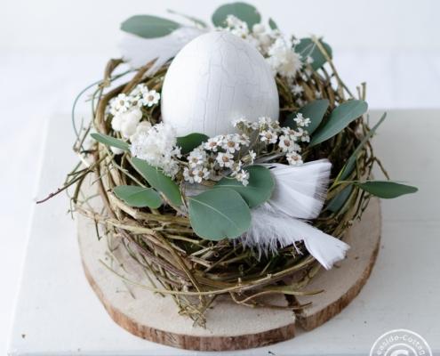 Dekoidee für ein kleines Osternest mit Trockenblumen, Federn und Eukalyptus dekoriert