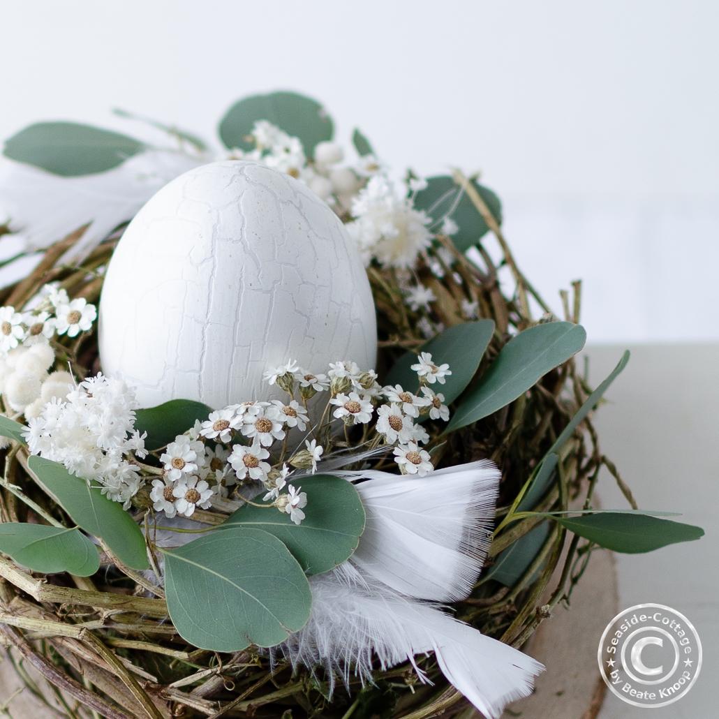 Weißes Ei in einem Nest mit Trockenblumen und Federn dekoriert