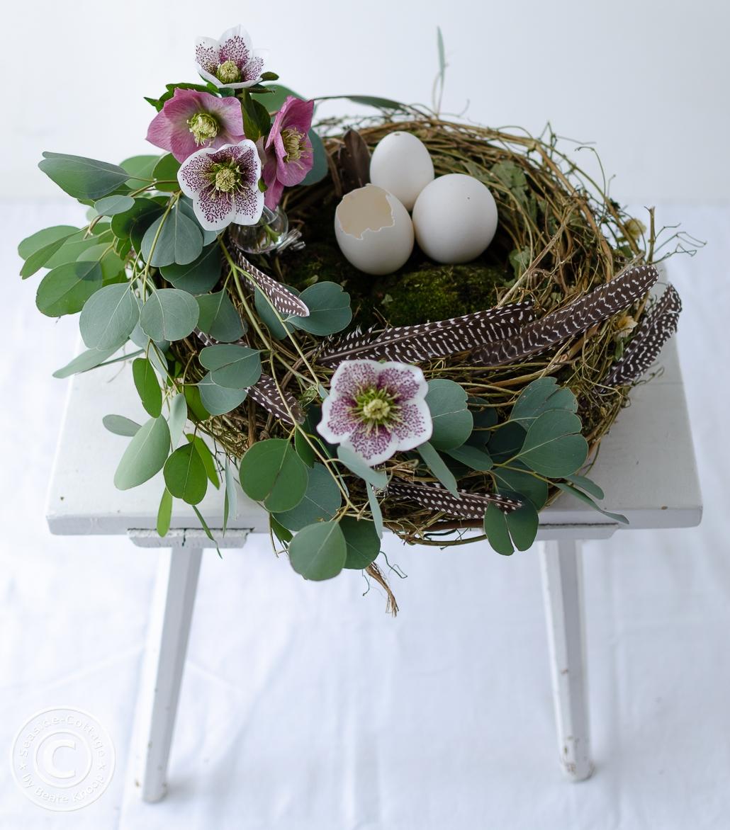 Nest aus Rebe auf einem weißen Holzhocker, dekoriert mit Eukalyptus, Lenzrosen, Moos und Gänseeiern