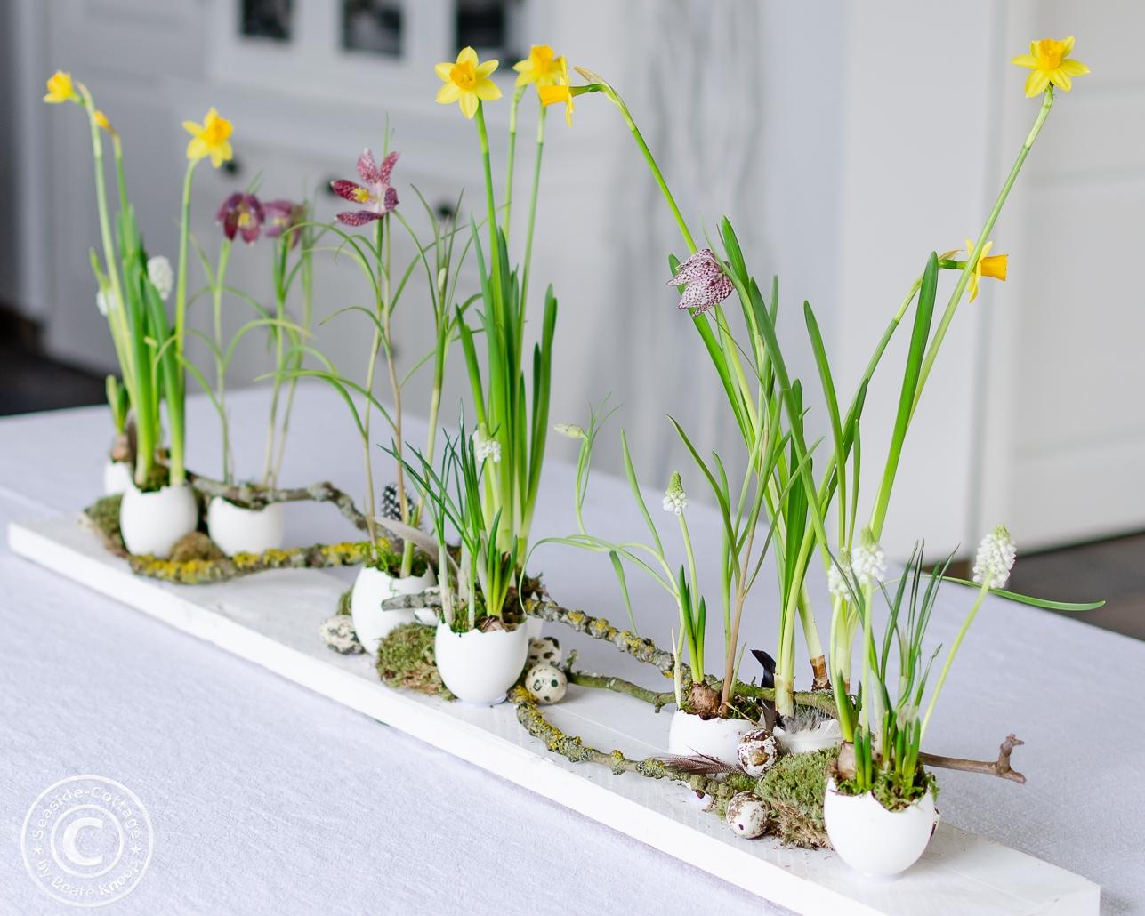 Tischdeko zu Ostern: Gänseeier auf einem Brett mit Eiern beklebt und mit Frühlingsblumen gefüllt