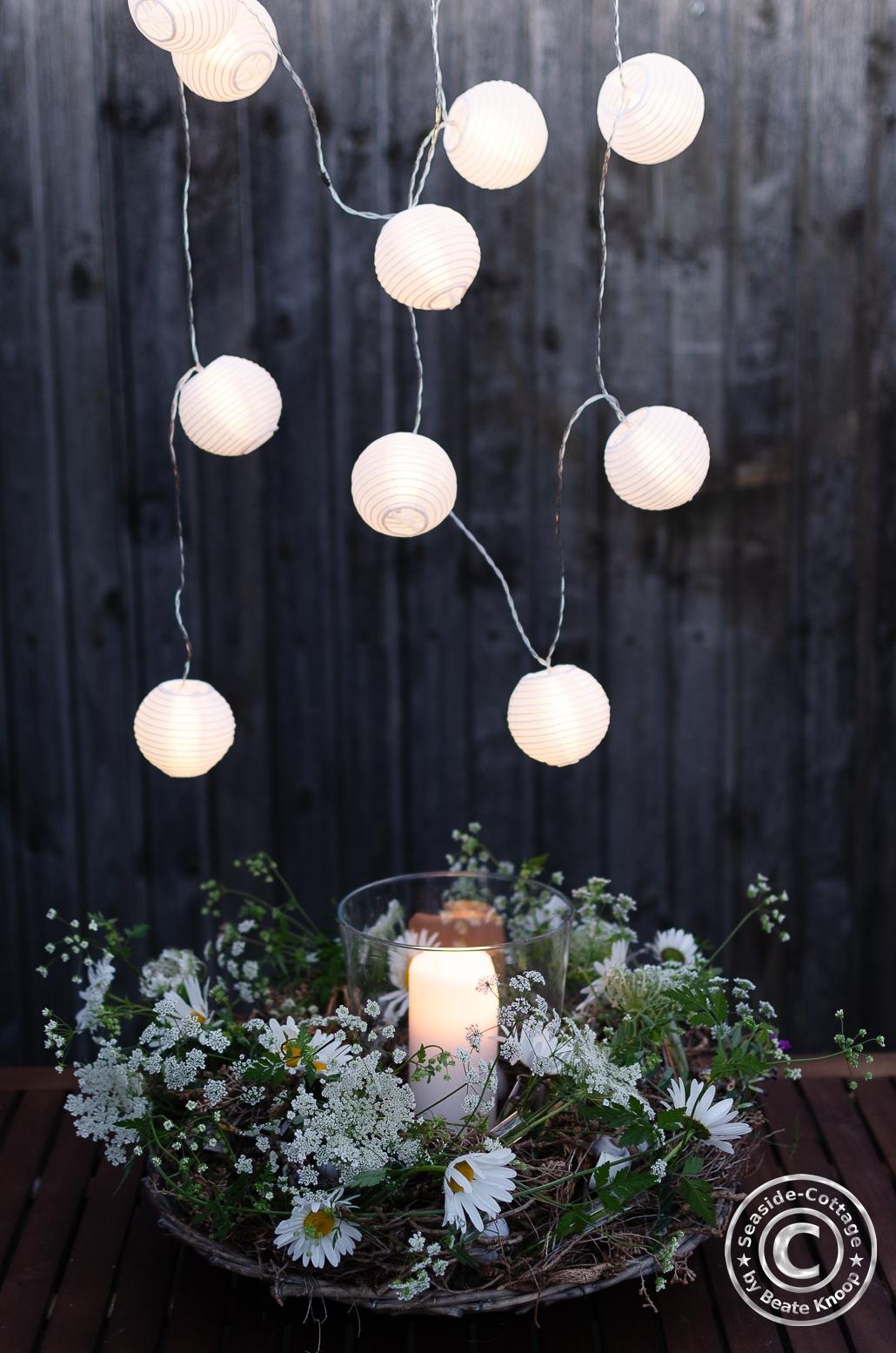 Abendstimmung mit Lichterkette, Windlicht und Sommerblumenkranz mit Wiesenblumen