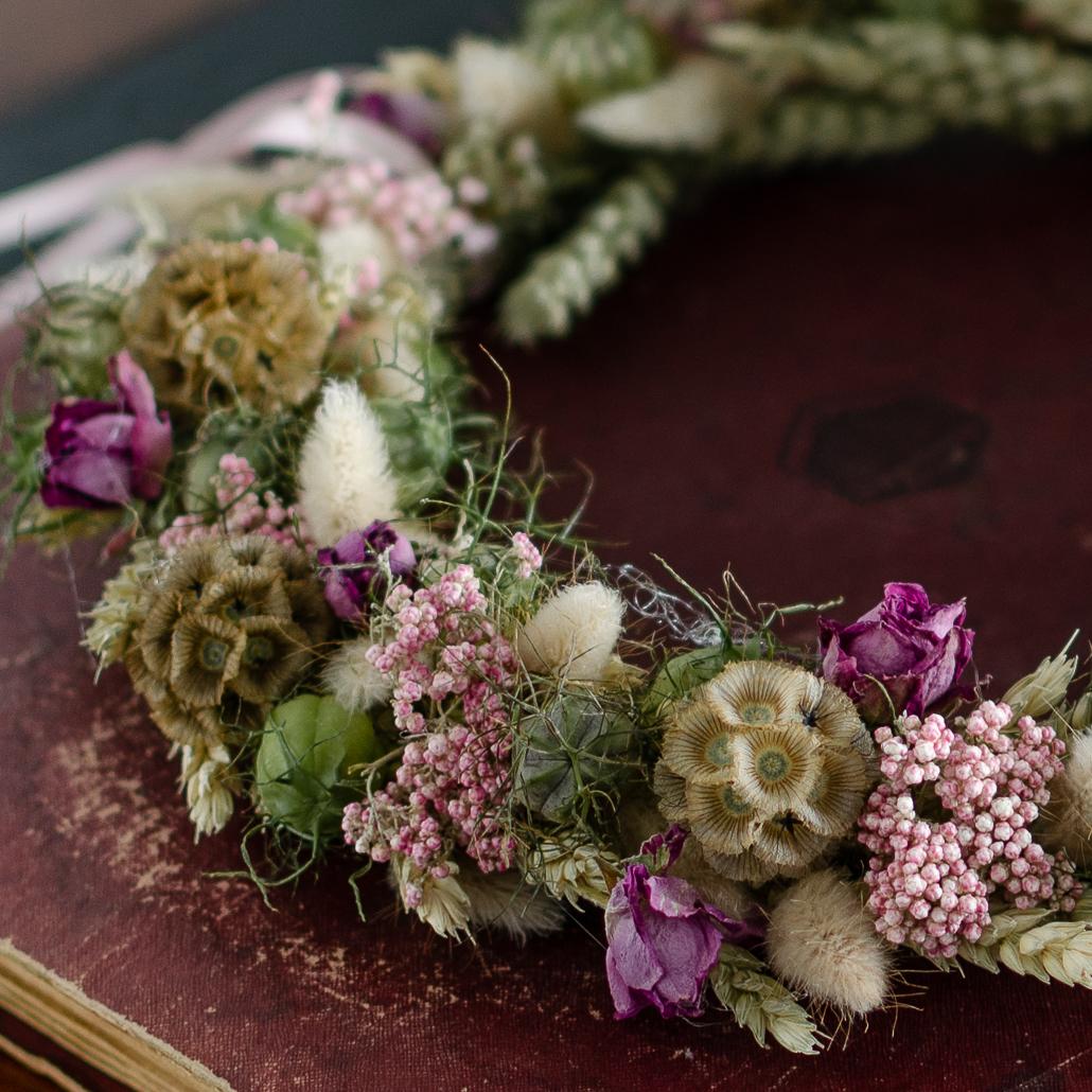 Nahaufnahme Trockenblumenkranz mit Nigella, Weizen, Gräsern, Scabiose, Schafgarbe und Rosen