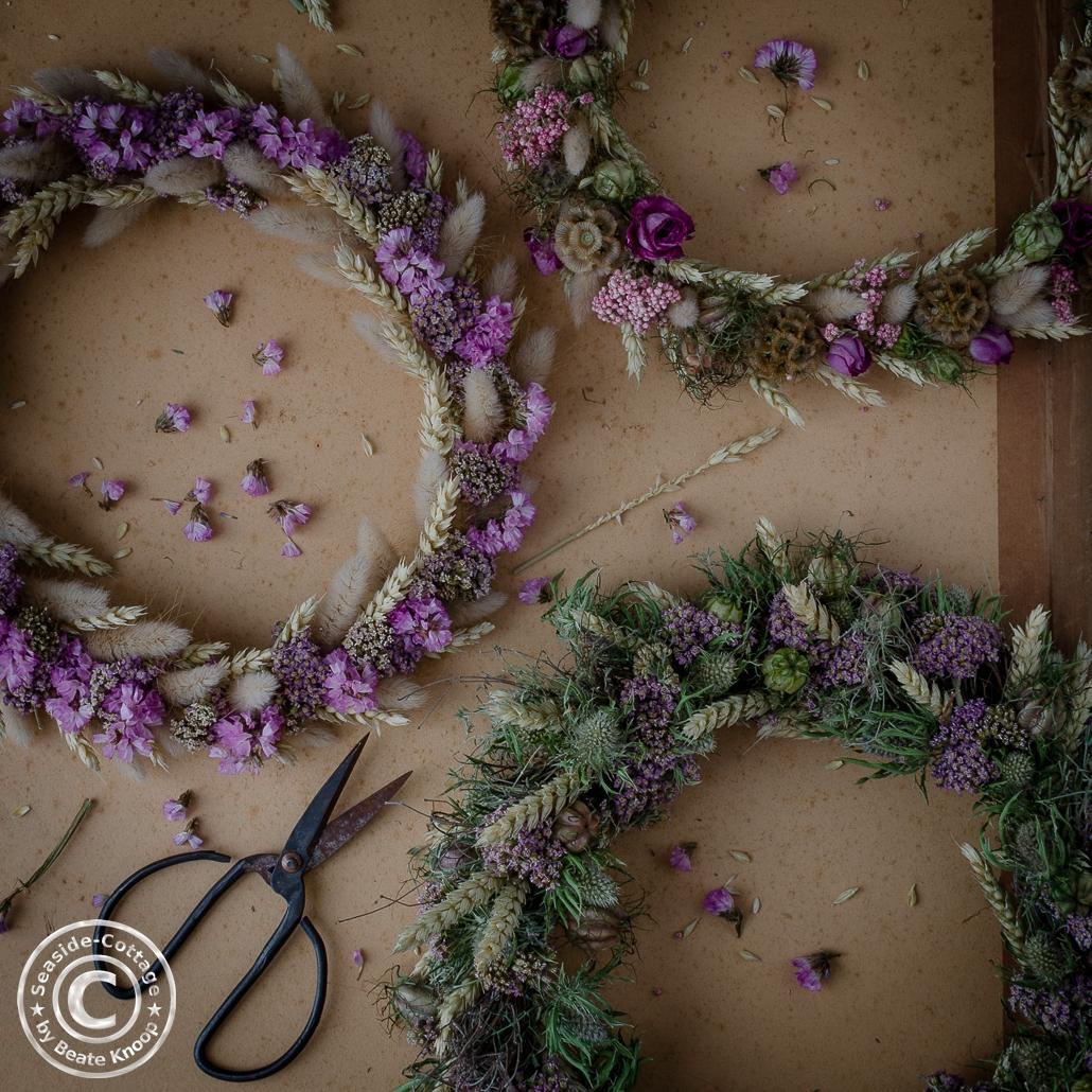 Drei Trockenblumenkränze mit einer alten Blumenschere