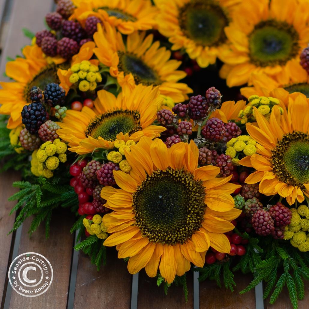 Nahaufnahme Sonneblumenkranz mit grünen Ranken, Brombeeren und Rainfarn