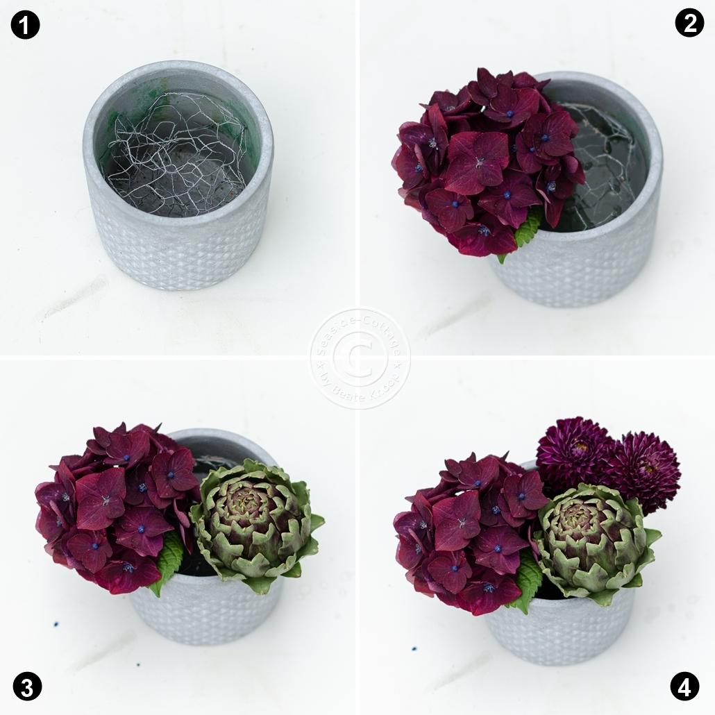 Anleitung in 4 bebilderten Schritten, wie man ein Tischgesteck in einem runden Gefäß steckt. Dabei wird statt Steckschaum Maschendraht verwendet. Blumen: Hortensie, Artischocke, Dahlien