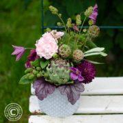Sommerliche Tischdeko mit Artischocke, rosa Rosen, Hortensie, Dahlien, Waldreben, grünen Brombeeren und Wiesenknöpfchen