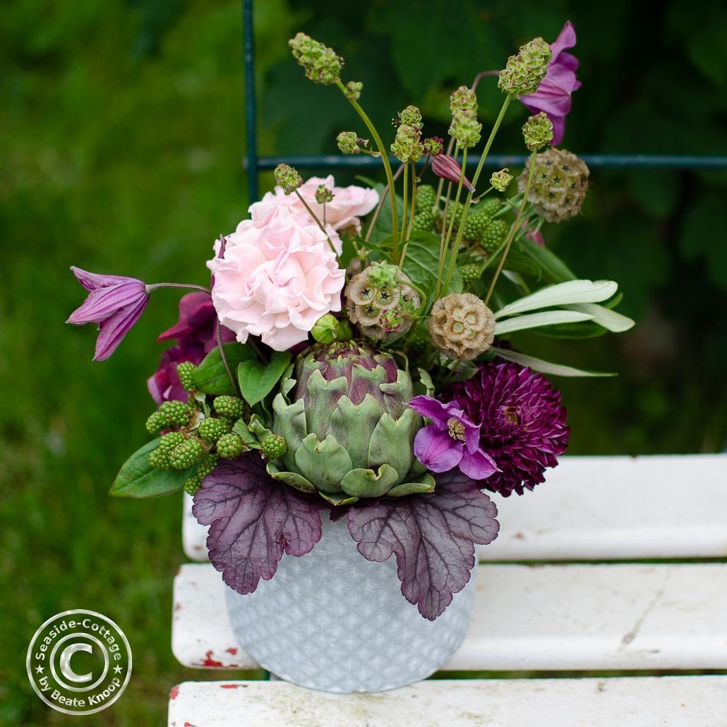Sommerliches Blumengesteck in den Farben rot-violett-grün