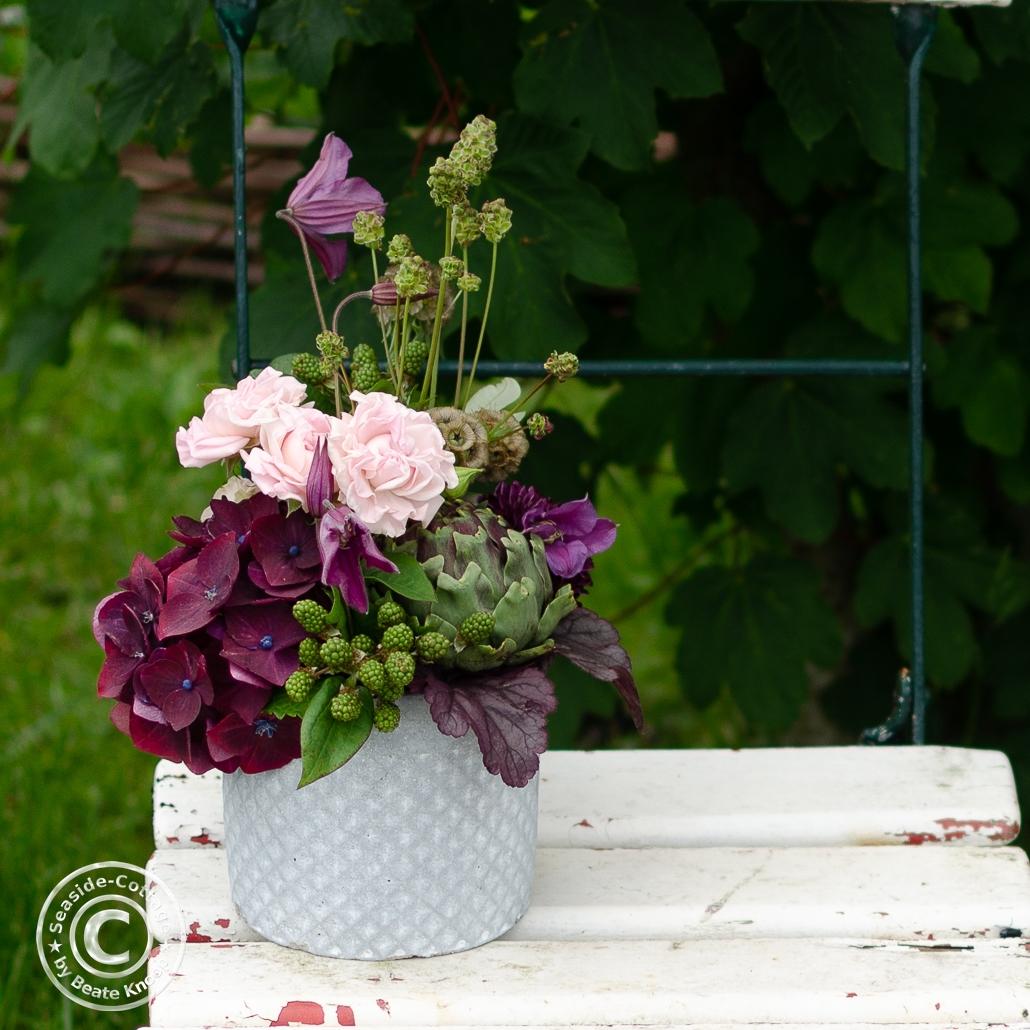 Sommerliches Blumengesteck in einem Betontopf auf einem alten Gartenstuhl stehend