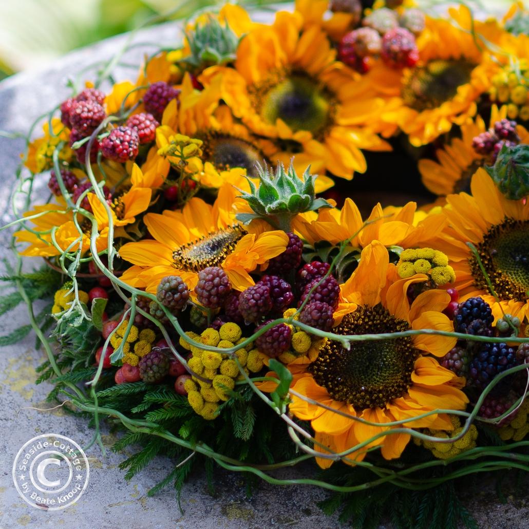 Nahaufnahme KRanz mit Sonnenblumen, Brombeeren, Rainfarn und grünen Ranken