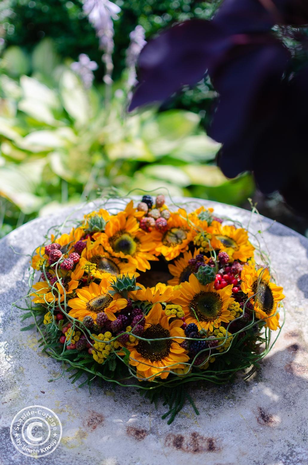Sonnenblumenkranz im Garten auf einem Gartentisch