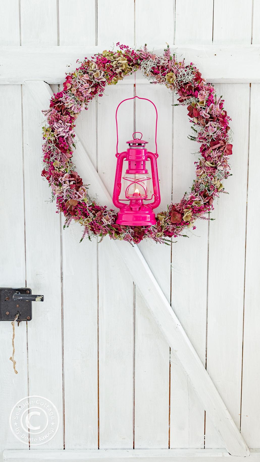 Großer Hortensienkranz an einer weißen Holztü hängenta mit einer pinkfarbenen Feuerhand Stumrlaterne Baby Special 276