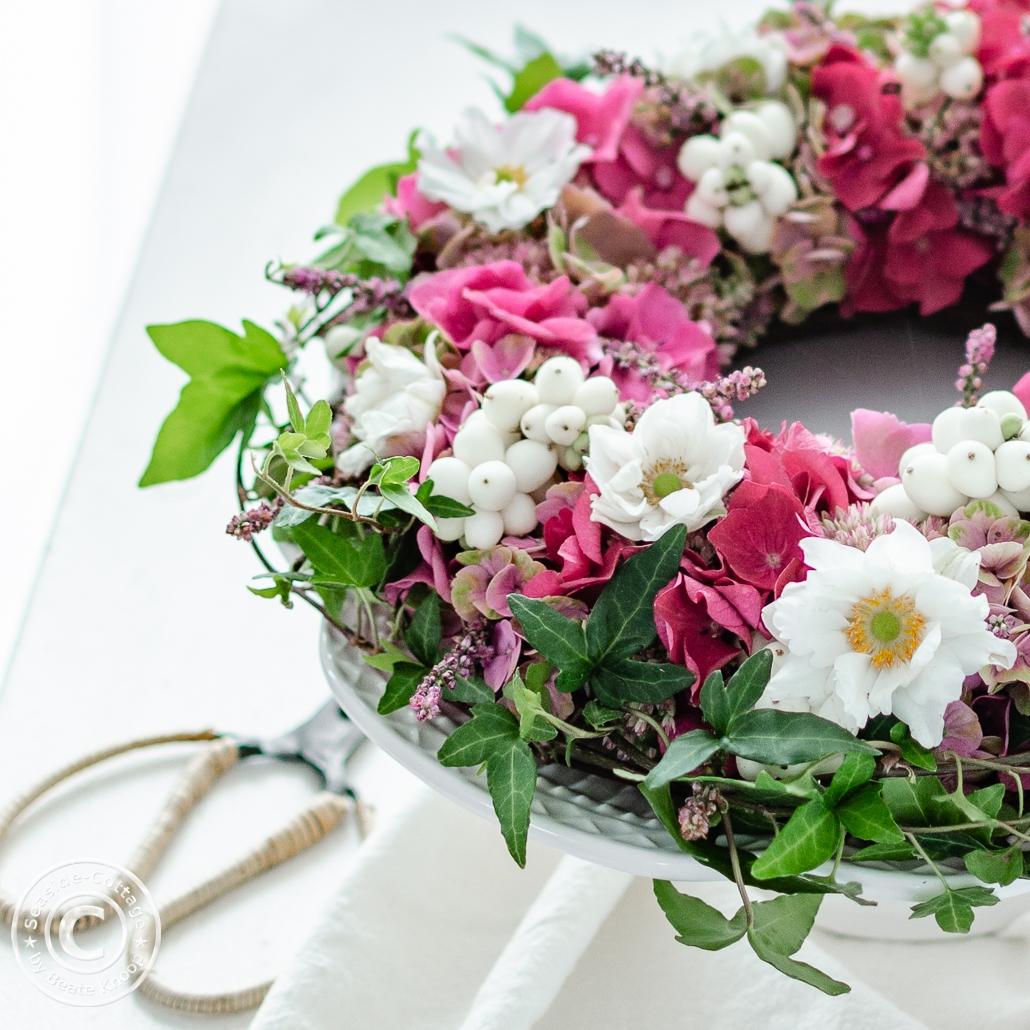 Nahaufnahme rosa-weißer Hortensienkranz mit Herbstanemonen