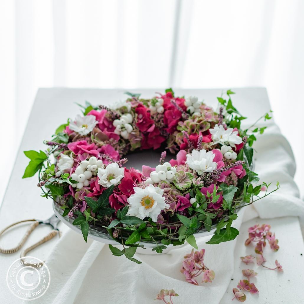 rosa Hortensienkranz mit Herbstanemonen auf Tisch mit weißer Tischdecke vor einem Fenster mit weißer Gardine