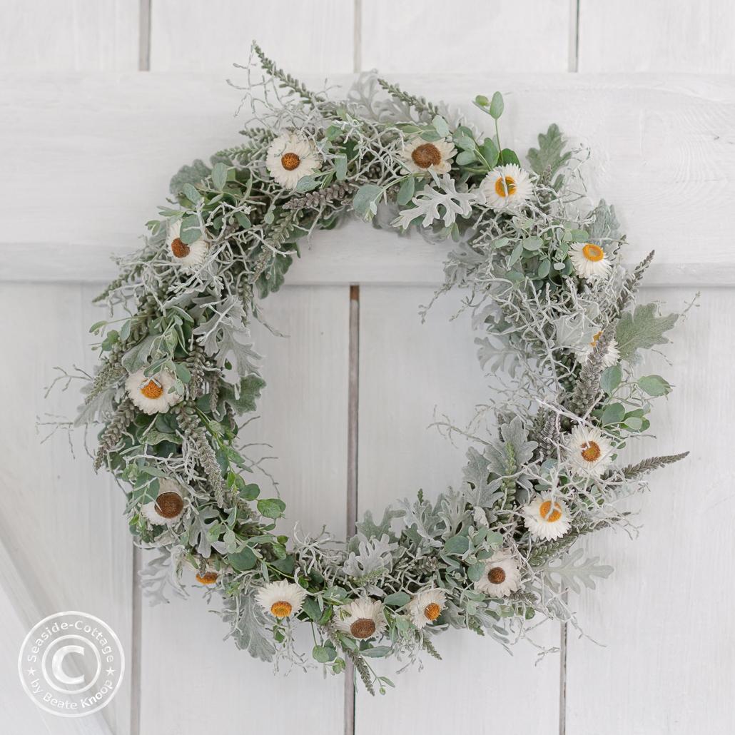 Kranz in Grau-Weiß mit Heidekraut, Silberblatt, Eukalyptus, Calocephalus und Strohblumen hängt an einer weißen Holztür