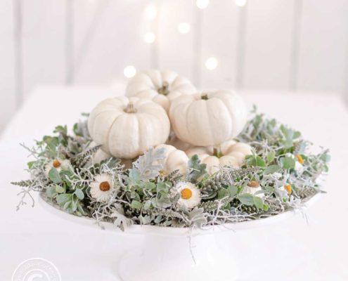 weiße Tortenplatte auf Fuß dekoriert mit einem grau-weißen Herbstkranz und kleinen weißen Zierkürbissen, im Hintergrund das Bokeh einer Lichterkette vor einer weißen Bretterwand