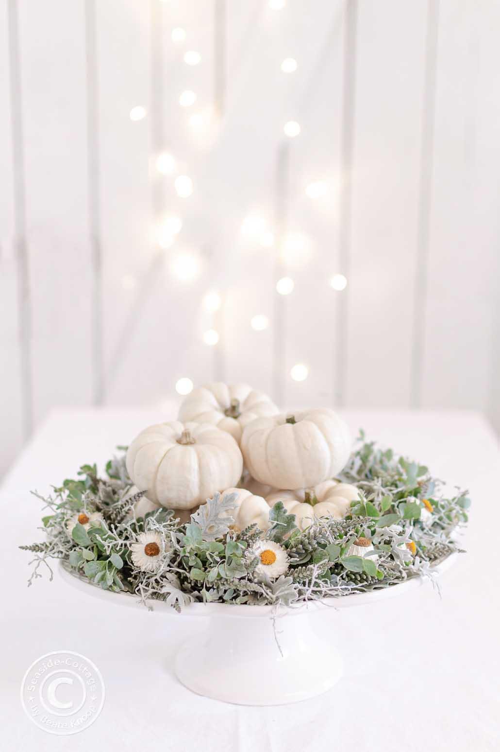 weiße Trotenp0latte aus Keramik mit Fuß auf einem Tisch mit weißer Tischdecke, im Hintergrund eine weiße Bretterwand mit Lichterkette. Auf der Tortenplatte ist ein Herbstkranz in grau-weiß dekoriert, in dessen Mitte sind kleine weiße Zierkürbisse gestapelt
