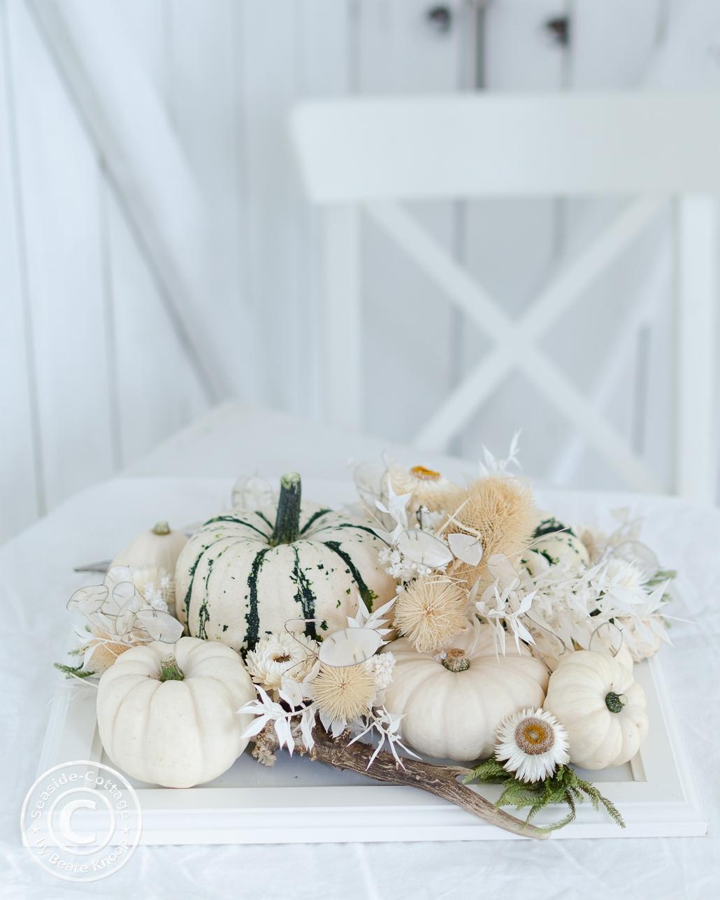 Herbstliche Tischdeko mit Kürbissen in weiß und weiß-grün mit Trockenblumen in naturtönen und Weiß, auf einem weißen Tisch dekoriert, hinter dem ein weißer Stuhl steht
