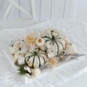 Tischdeko mit weißen Kürbissen und Trockenblumen auf einem weißen Tisch mit weißer Tischdecke