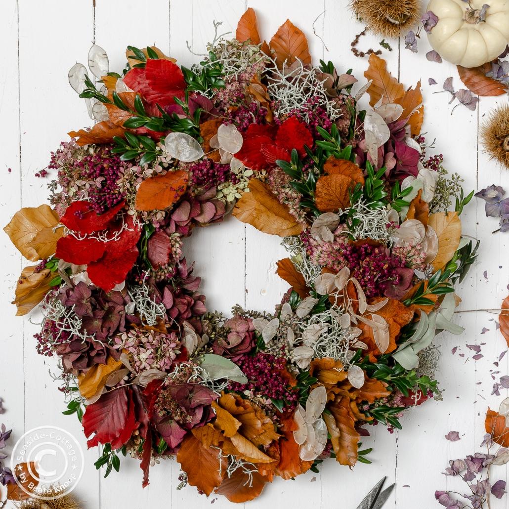 Bunter Herbstkranz auf weißen Holzbrettern