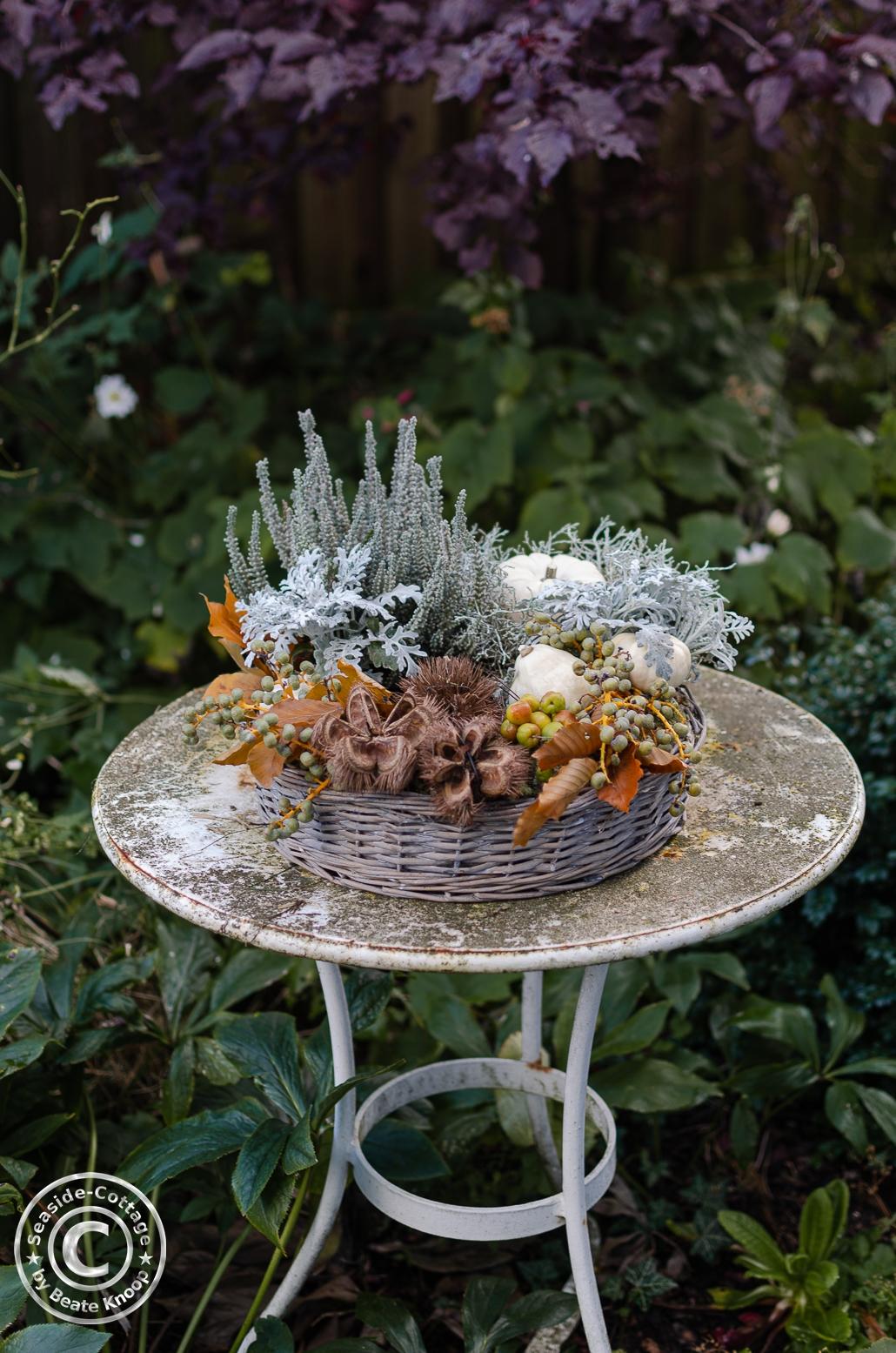 Pflanzring herbstlich dekoriert mit Naturdeko, auf einem verweitterten Gartentisch arrangiert