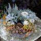 herbstliche dekorierter Pflanzring auf einem verwittertem Gartentisch