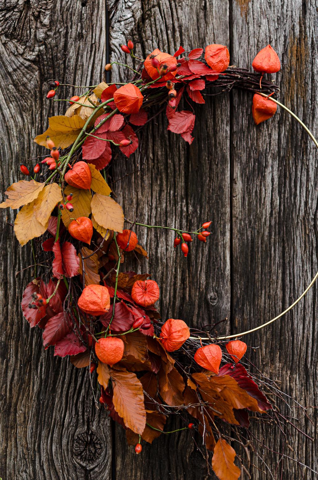 bunter Herbstkranz halb auf goldenem Ring gebunden, hängt an rustikalen Eichenbrettern