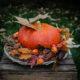 Herbstdeko: Großer oranger Kürbis auf Korbtablett, dekoriert mit Herbstlaub, Ziermais und Physalis